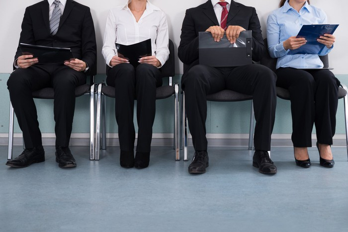 several people, shown from neck down, sitting on chairs next to each other, holding papers or materials that suggest they're waiting to be called in for an interview