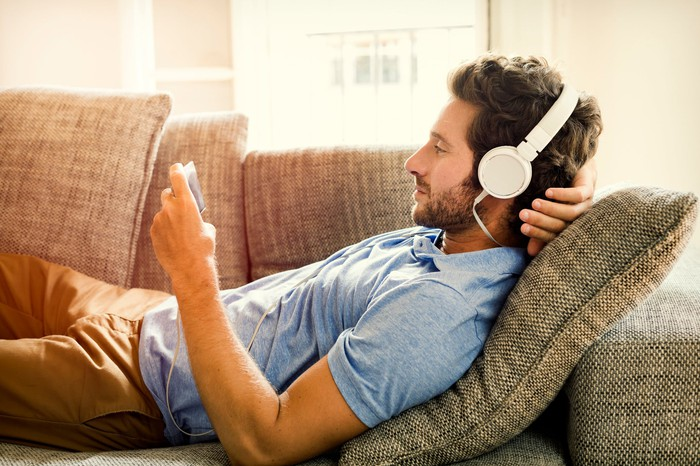 A man lying on the couch, wearing headphones, and looking at an electronic device.