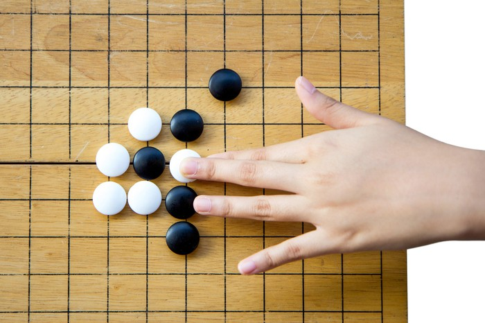A hand placing a white stone on a Go board