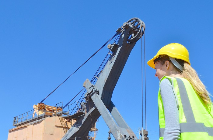 A woman in a hard hat and reflective vest standing in front of mining equipment