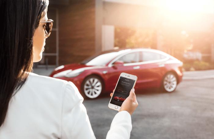 A woman using a Tesla mobile app to unlock Model 3.