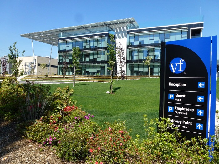 Glass-walled three-story building with grass lawn, flowers, and VF sign directing traffic to various parking lots.