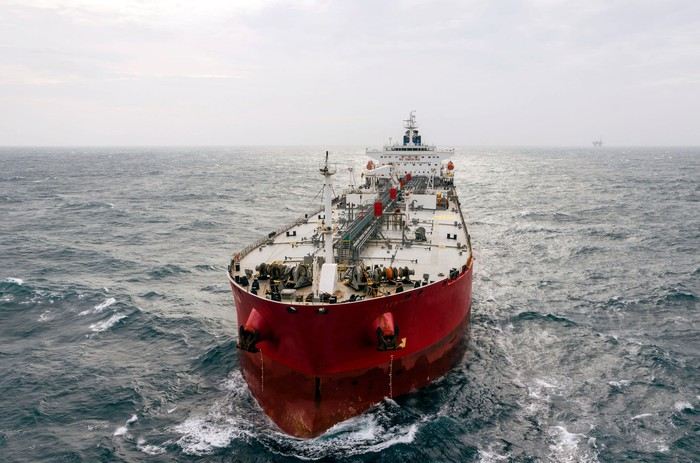 Red-hulled tanker vessel on a relatively calm ocean under a hazy sunny sky.