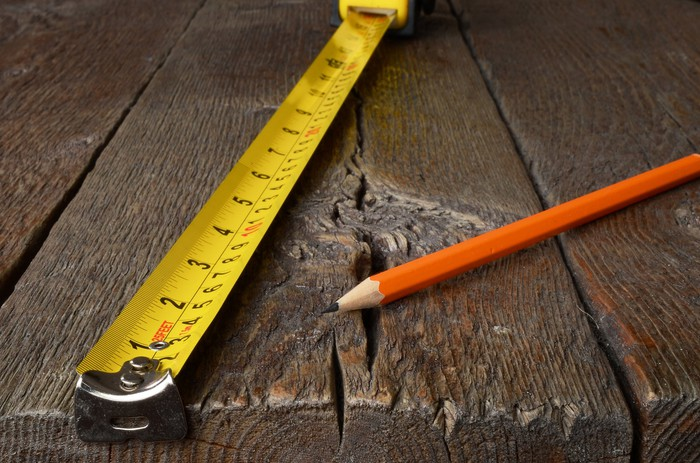 A tape measure and pencil on a wooden table