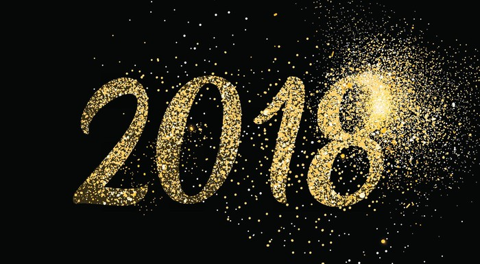Glitter-colored 2018 with explosion cloud on a black background.