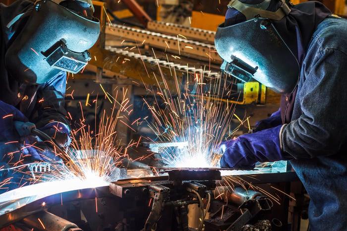 Two people welding.