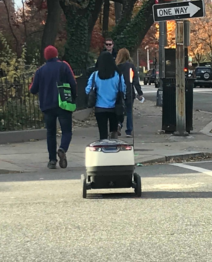 Small white robot on two wheels crossing the street and trailing three people