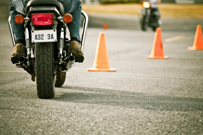 Motorcycle going through orange cones on a training course.