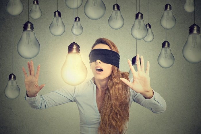 A blindfolded woman makes her way among hanging lightbulbs, seeking the bright one