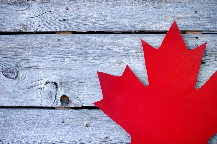 Cutout of red Canadian maple leaf on weathered picnic table.