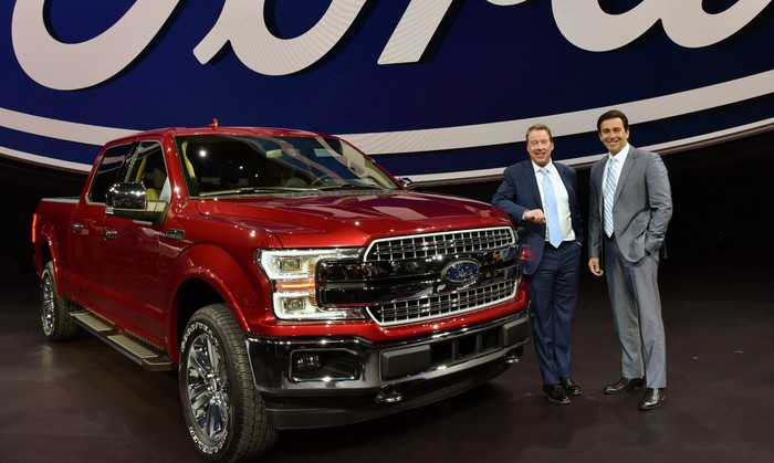 Bill Ford and Mark Fields are shown standing next to a red 2018 Ford F-150 pickup.