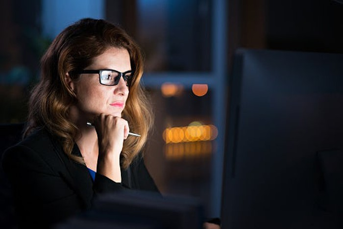 Picture of a woman at a desk looking intently at her computer screen.