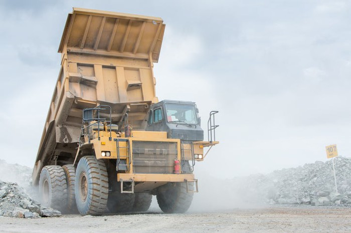 A giant earth mover truck leaving a mine.