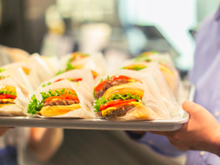 A hand holding a tray of Shake Shack burgers