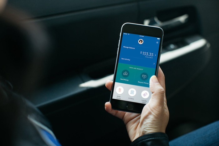 A person holding a smartphone with the PayPal app opened.