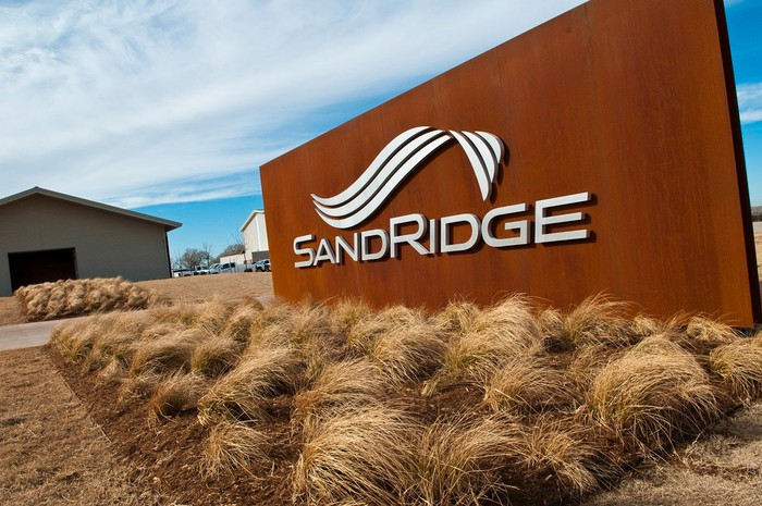 SandRidge logo on a wood-colored sign, with brush and industrial buildings in the background.