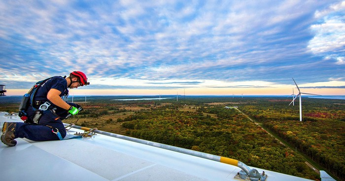 Worker on top of a wind turbine blade, with other wind turbines in a lightly forested area on a partly cloudy day.