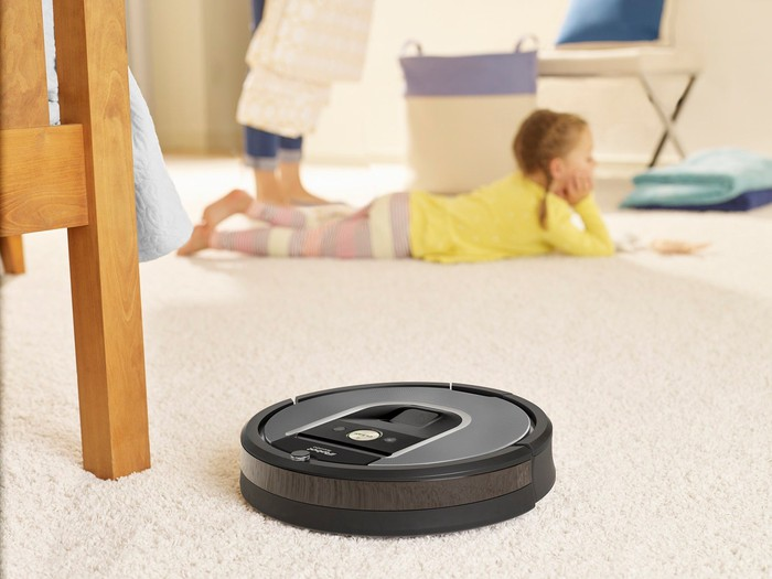 Roomba cleaning carpet with small child relaxing in the background