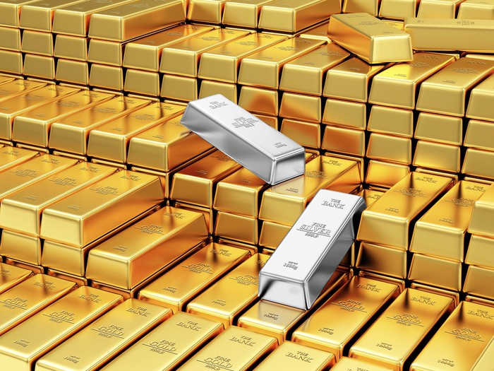 Two silver bars amid stacks of gold bars.