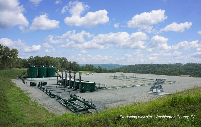 Natural gas well site with pumping and storage equipment, amid a green lawn and forest site under a partly cloudy blue sky.