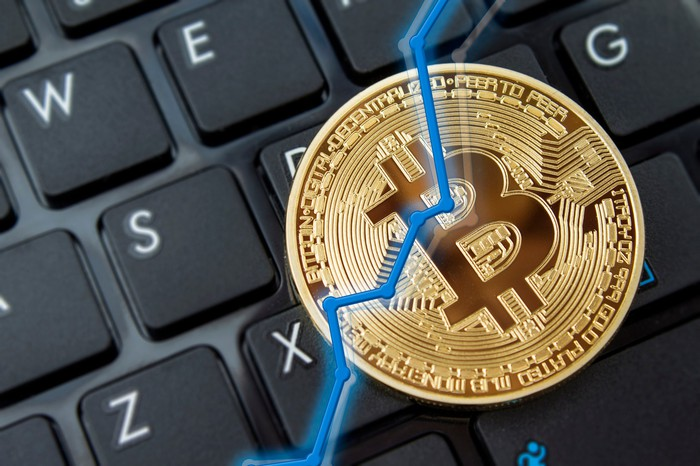 A rising stock chart overlaid on a physical gold bitcoin, with a keyboard in the background.