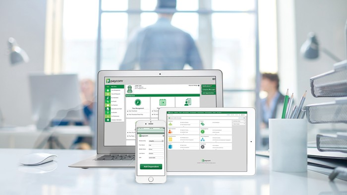 A variety of Paycom software screens on a laptop, tablet and smartphone.