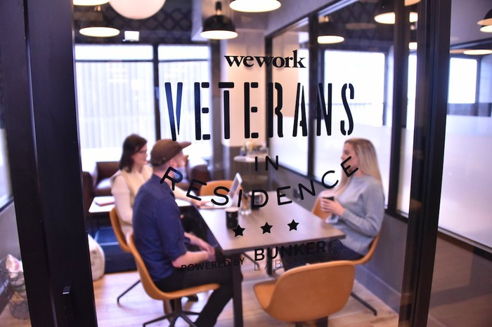"""A group of people meeting in a room labeled """"WeWork Veterans in Residence"""""""
