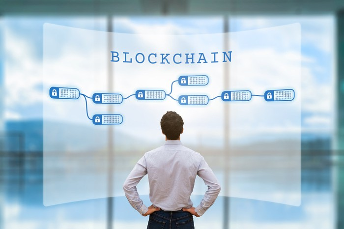 Businessman studies a wall-sized poster of a simple blockchain illustration, titled BLOCKCHAIN in capital letters.