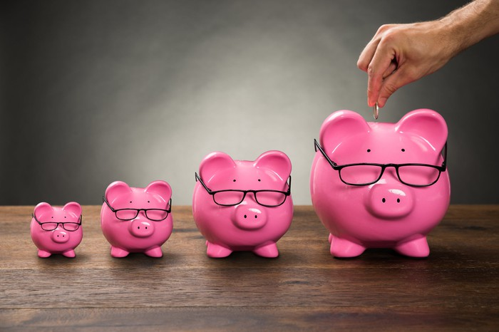 A row of progressively larger pink piggy banks wearing glasses with a man's hand holding a coin over the largest.