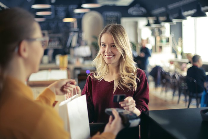A woman at checkout counter paying with a credit card