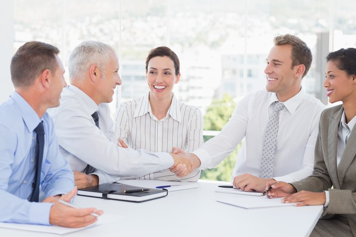 A group of professionally-dressed people sitting around a table smiling and shaking hands.