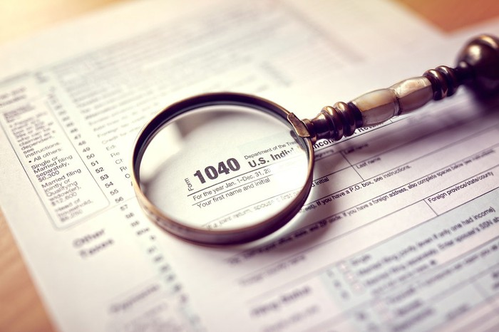 Tax returns on a wood desk with a magnifying glass on top of them.