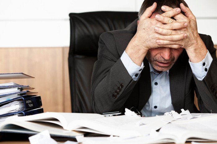 Professionally dressed man holding his head at his desk, as if stressed