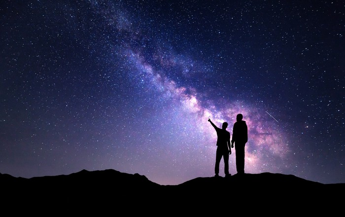 Father and son gazing at the Milky Way galaxy