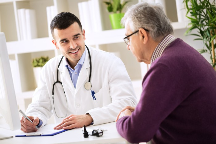 An older man and a medical professional in a white coat discussing something while the medical professional writes on a clipboard.