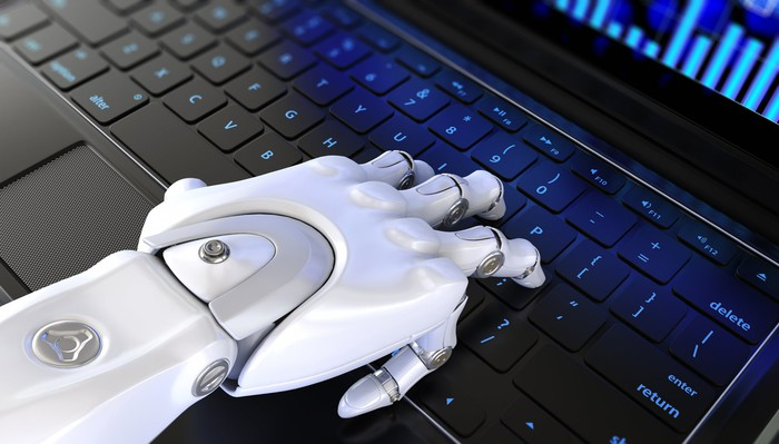 A robot hand on a keyboard.