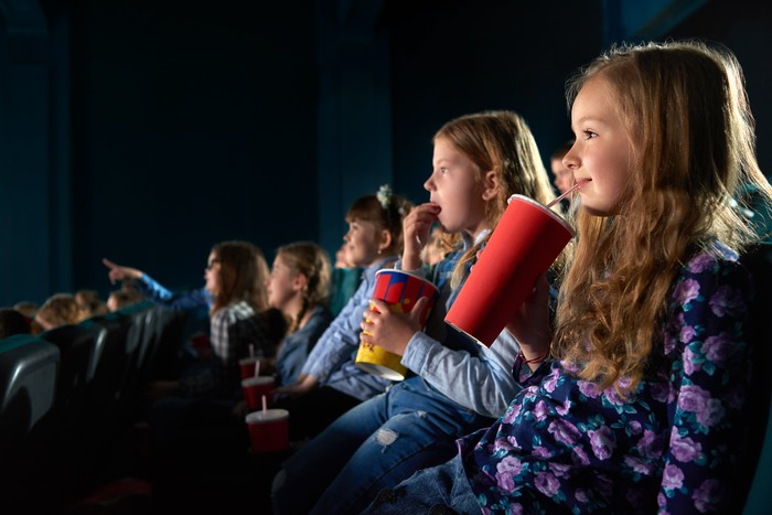 Kids watching a movie at a theater.