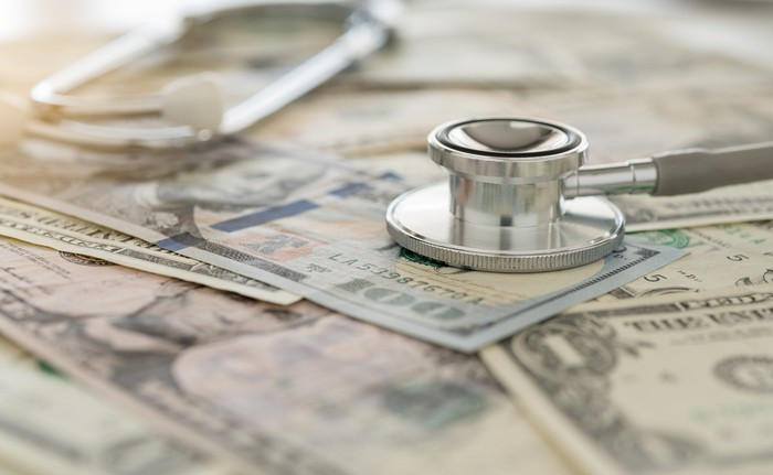 A stethoscope sits on top of a scattered pile of U.S. currency.