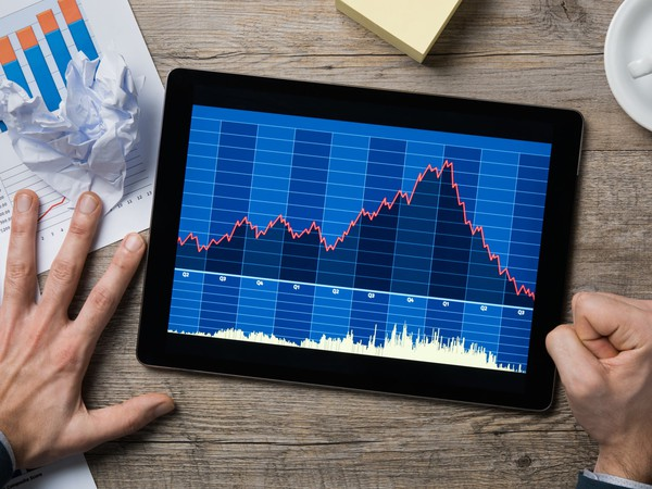Man looking at declining share price chart on tablet and pounding fist on table stock broker market crash bear correction