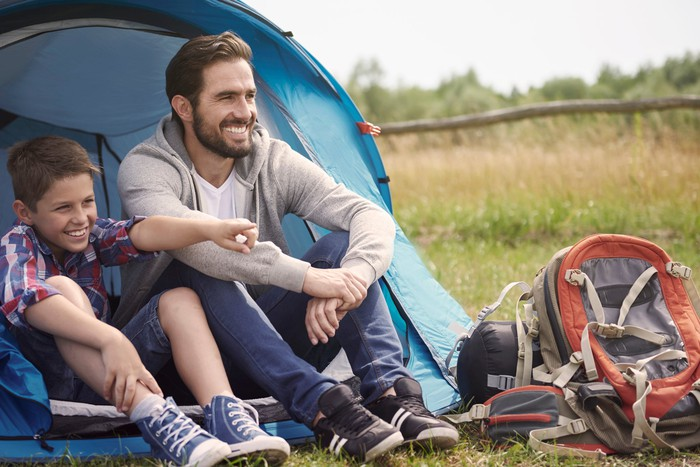 Man and boy sitting in front of tent