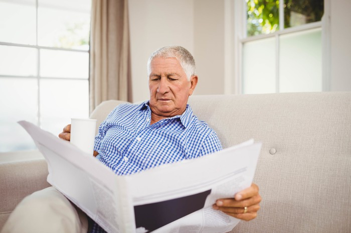 Senior male reading the newspaper with mug in hand
