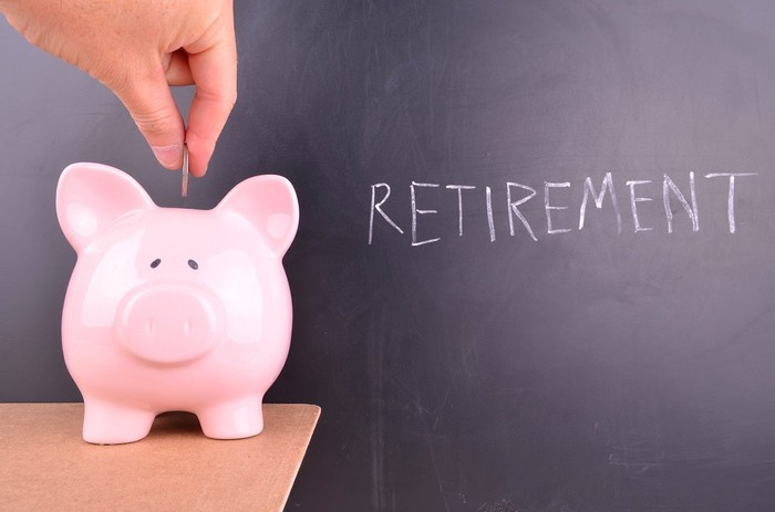 "Hand placing change in a piggy bank next to the word ""retirement"" on a chalkboard."