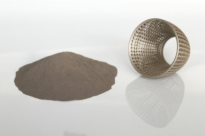 A pile of metal powder next to a 3D-printed metal part.