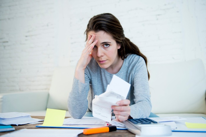 Woman sitting at a cluttered desk, putting a hand to her head while clutching a stack of papers.