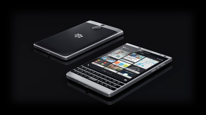 BlackBerry mobile device, shown with cover and with face revealed, against a black background.