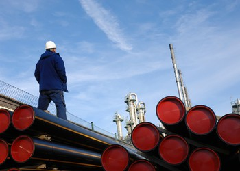 A person in a hardhat standing near a stack of pipelines.