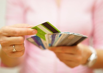 woman holding handful of credit cards debt