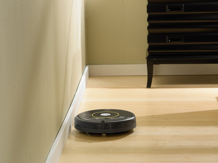 The iRobot Roomba 650 self-piloting vacuum cleaner cleaning a wood floor.