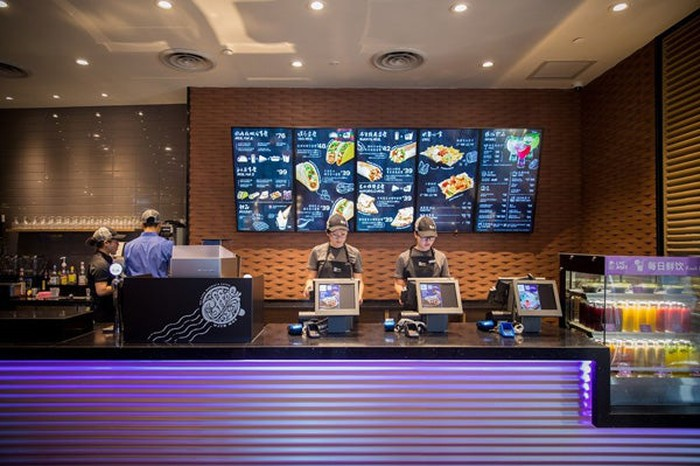 The inside of the first Taco Bell in Shanghai. Two employees stand behind the ordering counter in front of computers, with a menu displayed on the wall behind them.