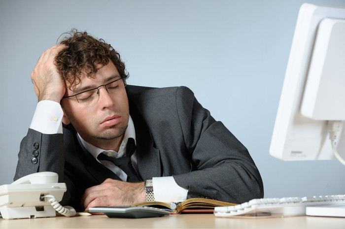 Professional male falling asleep at his desk